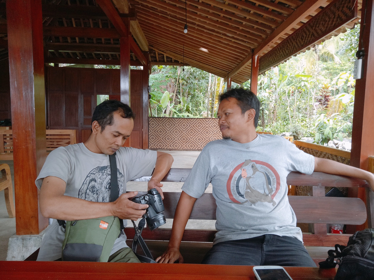 Suparno (left) and Arif take a break and review photographs of Jatimulyo's birds.