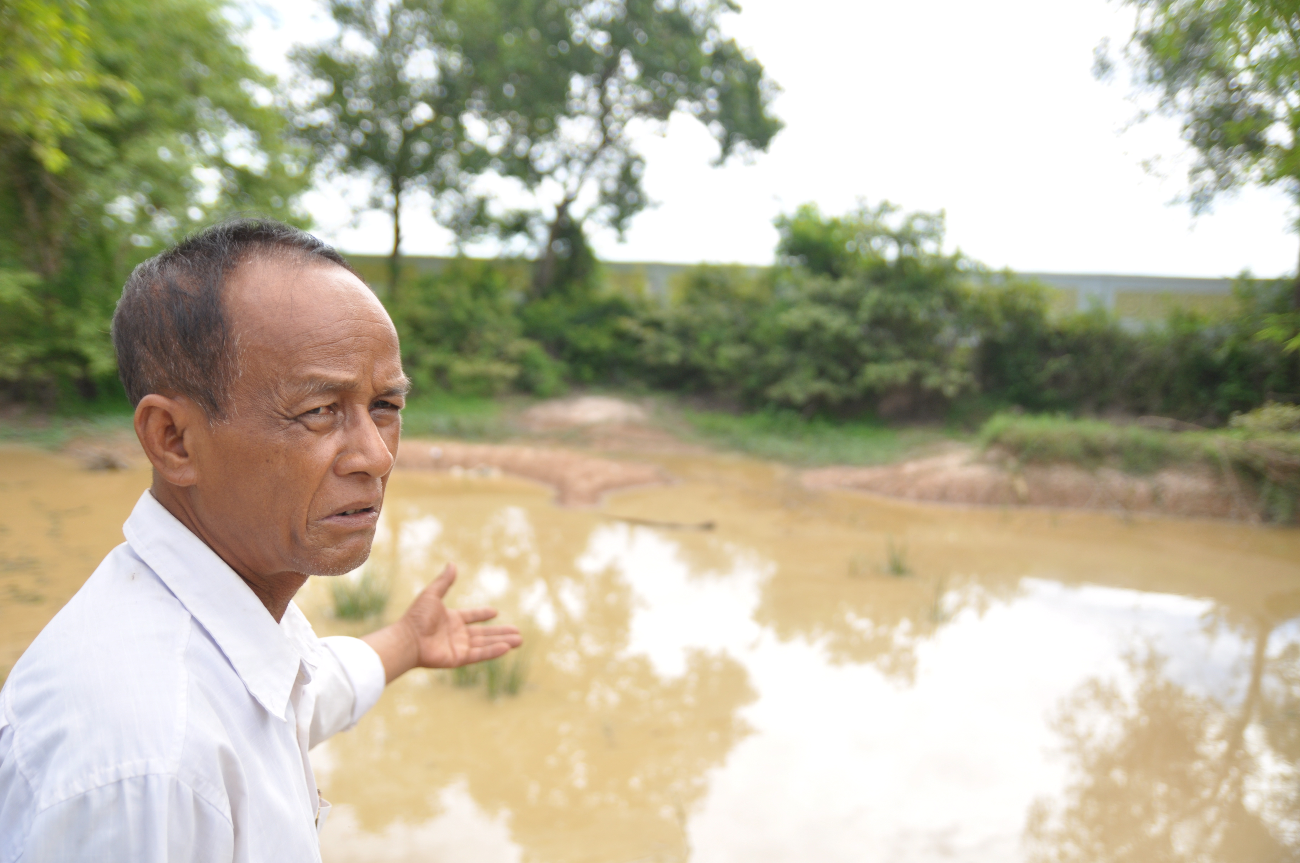 Tun Soun, a Khmer Krom survivor, points to one of the mass grave sites near Wat Pratheat (pagoda) in Kiri Vong district, Takeo province. The area was one of Cambodia's most notorious prison and torture centres.