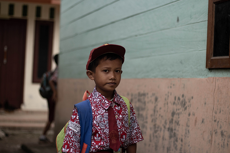 A primary school boy wearing a state school uniform that is consists of a batik top.