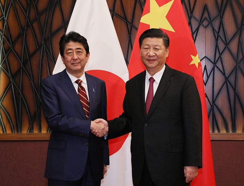 a picture of shinzo abe and xi jinping shaking hands in front of their respective countries' flags.
